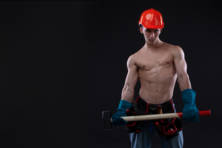 Handsome young topless construction worker in helmet with sledge hammer, studio shot, black background. builder. Copy space