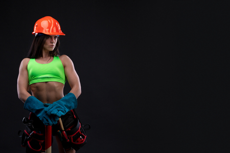 sexy female miner worker with pickaxe, in coveralls over his naked body