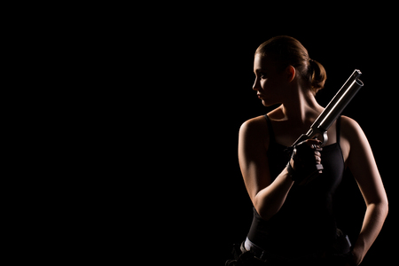 Military sexy woman with a sport gun over black background. Copy space