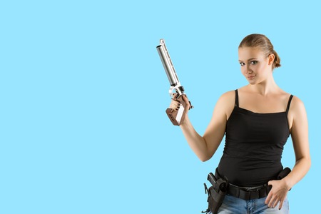 Young beautiful sexy blond Woman holding sport Handgun in hand on blue background. Copy space