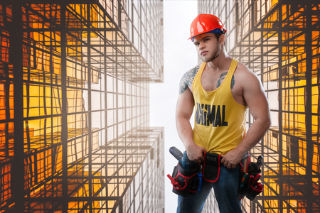 Strong build construction worker against the background of the mutallic structures. Copy space 스톡 콘텐츠
