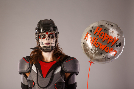 Happy halloween. hockey player in a hockey helmet and mask with a balloon against the isolated backdrop or background. holiday halloween. All Saints Day
