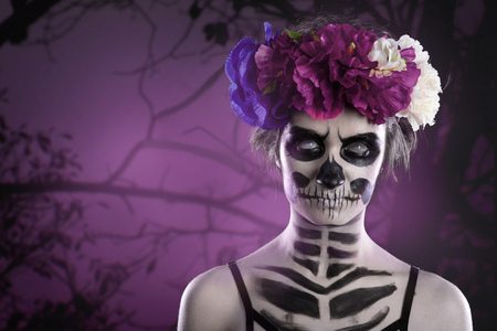 attractive woman with sugar skull make-up in front of creepy forest scene with full moon. Copy space