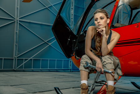 helicopter maintenance femail worker. woman pilot or helicopter mechanic holding the adjustable wrench. woman is tired after work Banque d'images - 108656760
