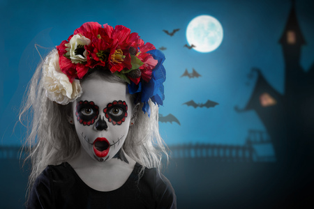 Portrait of a young girl in a make-up on a Halloween wreath with red flowers on her head. against a terrible sky Stock Photo