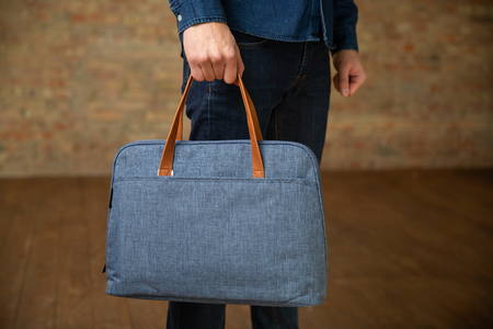 Man hold on a textile briefcase for a laptop. Archivio Fotografico