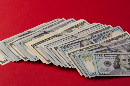 Stack of one hundred dollar bills new and old design on red background. casino bet