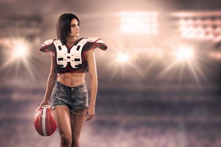 Eine Sportlerin posiert mit American-Football-Ausrüstung im Stadion. Die Spielerin hält einen Helm in der Hand Standard-Bild