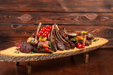 Mixed Grilled meat and vegetables on wooden background. restaurant feed Reklamní fotografie