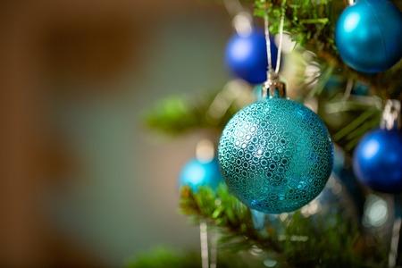 Blue Christmas ball on Christmas tree. New Year concept. Macro.