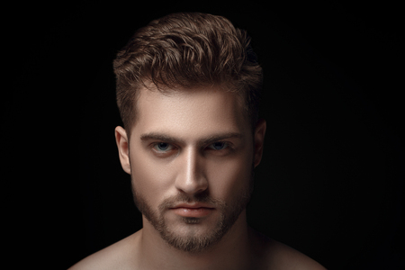 Closeup view portrait of one handsome bearded young macho man with strong look hazel eyes and lips standing in light looking forward