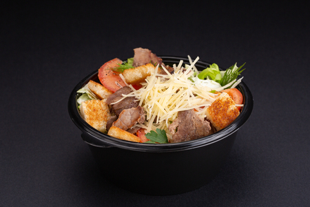 Salad with beef, spinach, tomatoes and Parmesan cheese. On a black background.