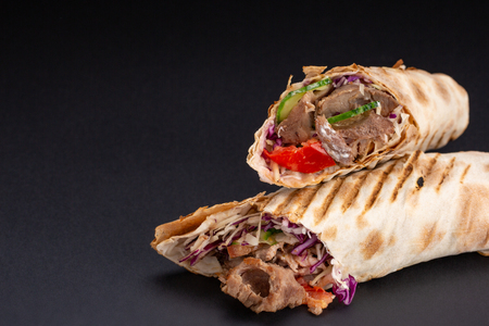 Shawarma sandwich - fresh roll of thin lavash or pita bread filled with grilled meat, mushrooms, cheese, cabbage, carrots, sauce, green. Traditional Eastern snack. On a black background.
