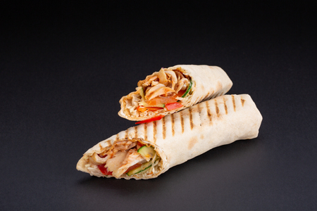 Shawarma sandwich - fresh roll of thin lavash or pita bread filled with grilled meat, mushrooms, cheese, cabbage, carrots, sauce, green. Traditional Eastern snack. On a black background. Banque d'images