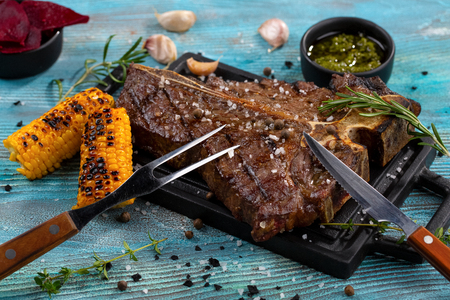T-bone beef stake served on a cutting board with sauces, rosemary, corn grill