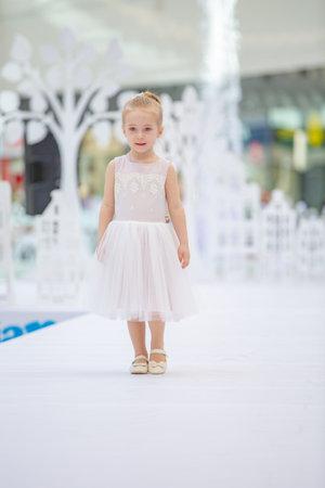 Kyiv, Ukraine March 03.2019. UKFW. Ukrainian Kids Fashion Day. Little girl model weared at pastel dress posing at the podium at the fashion show