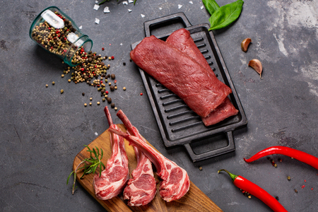 Set of Raw uncooked black angus beef tomahawk steaks on bones and veal tenderloin served with chilli and peppercorns. Rustic style. Close up Stok Fotoğraf