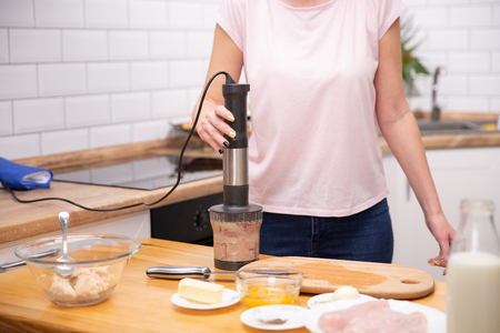 Woman using a hand blender to make a pate. cooking process