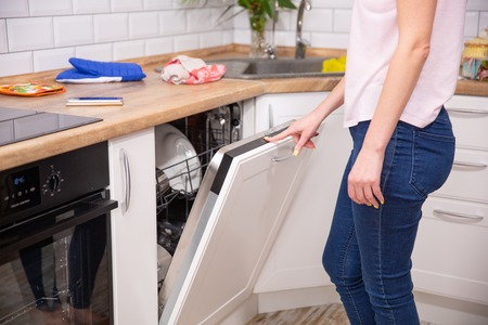 Washing dishes in the dishwasher. The woman puts dirty dishes in the dishwasher. Opening and closing the dishwasher. The woman cares about the house, does his homework