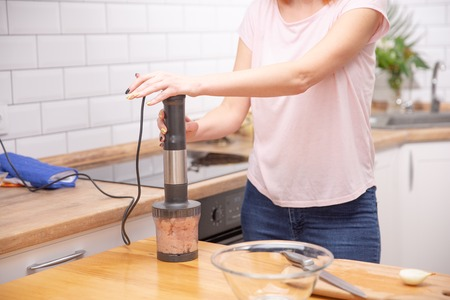 Woman using a hand blender to make a pate. cooking process Standard-Bild