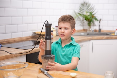 Cute toddler boy using hand blender to make minced meat. Preparing meal in the kitchen. Little boy learns to cook
