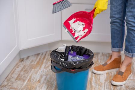 la femme au foyer jette des fragments d'une assiette cassée à la poubelle. Nettoyage à la maison