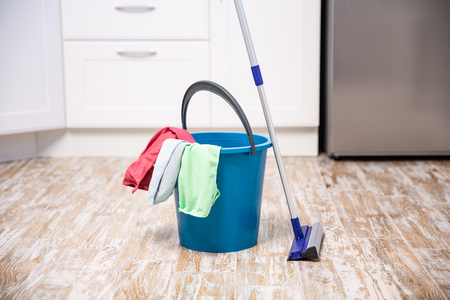 Plastic bucket with cleaning supplies in home. cleaning the kitchen