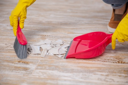 Clean up broken plate with broom and dustpan. sweep up the splinters