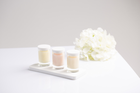 three jars of skincare candle cream with natural fresh summer flowers at light background Stok Fotoğraf - 121238853