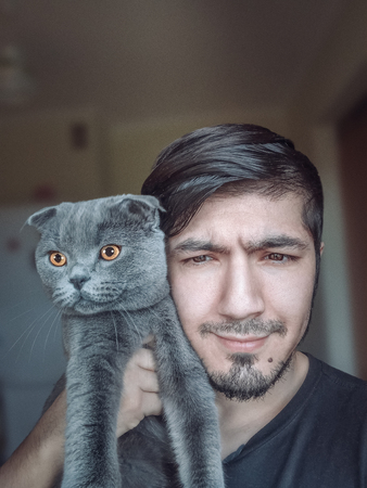 Scottish Folds are hardy cats and their disposition matches their sweet expression. They adore human companionship and display this in their own quiet way. Portrait of man and scottish fold cat Reklamní fotografie