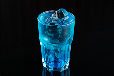 Blue cocktail drink with ice cubs on black Stockfoto