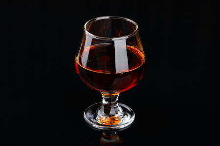 Glass of brandy or cognac on a black