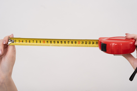 A female hands hold a yellow tape centimeter measure on white, top view at the studio.