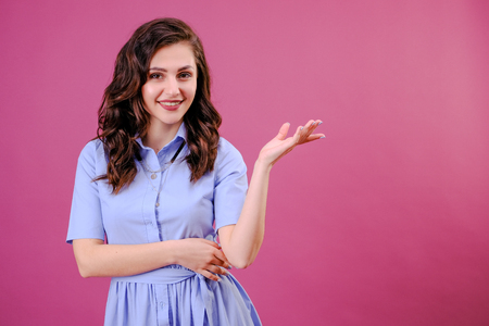 A beautiful girl who smiles and shows gestures on a pink background