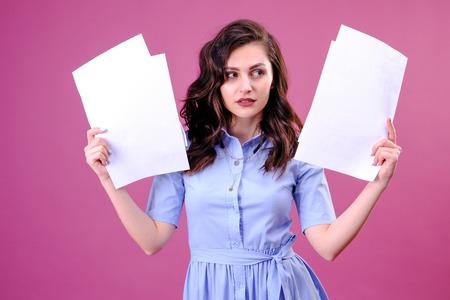 Junge kaukasische brünette Frau, die Papier über rosafarbenem Hintergrund hält, erschrocken mit einem Überraschungsgesicht, ängstlich und aufgeregt mit Angstausdruck