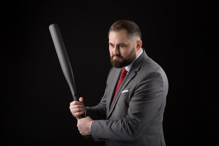 bearded Man in suit and red tie with baseball bat on black background