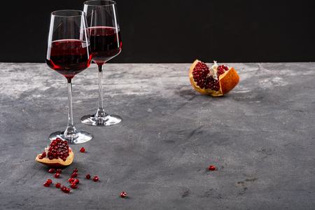Red garnet, pomegranate and garnet red wine. Two glasses. Copy space