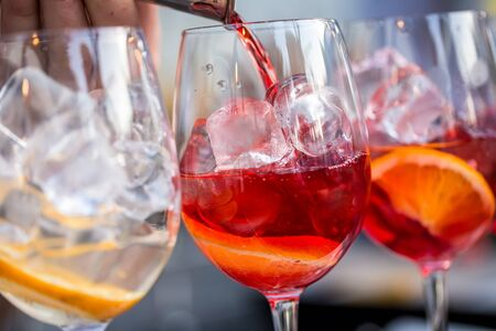 Glasses of cocktails on the bar. bartender pours a glass of sparkling wine with Aperol.