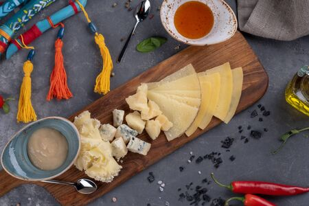 different sliced cheese is on a wooden plate with sauces on stone background Фото со стока