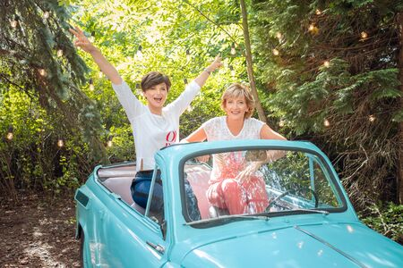 Two women in a vintage car. happy senior mother and adult daughter in a retro convertible