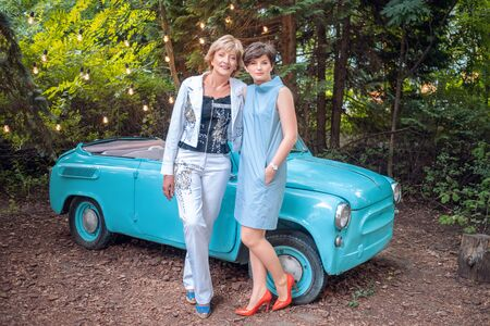Two women in a vintage car. happy senior mother and adult daughter stand by a retro convertible Фото со стока