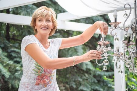 Senior Woman changing a light bulb in a chandelier