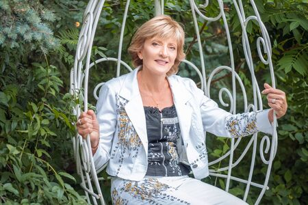 Portrait of a smiling mature woman sitting on swing in the park