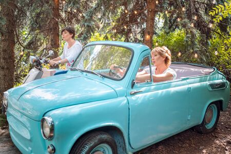 Two women in a vintage car. happy senior mother in a retro convertible and adult daughter on retro moped