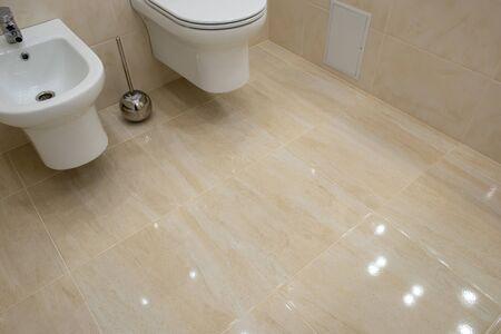 Toilet and bidet in a modern bathroom - raised lid. light interior Фото со стока