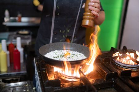 Cooking the Omelette in a pan and gas stove. street food.