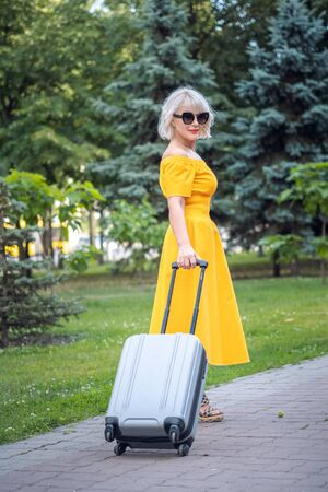 Back view of adult middle aged attractive business woman with wheel suitcase, happiness, success, travel concept Фото со стока