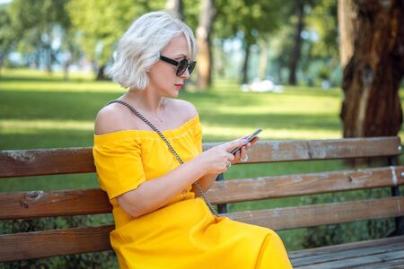 Beautiful adult middle aged blond woman in sunglasses using smart phone on the bench outdoors