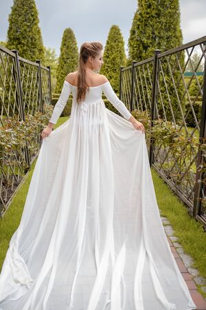 Princess in a vintage white dress. Walk along the picturesque summer field at sunset. Фото со стока