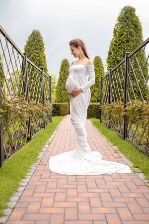 A beautiful and easy pregnancy. A long white train from the belly of a pregnant beautiful girl outdoor